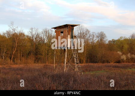 Makeshift old dilapidated hunting observation tower with cracked wooden boards and improvised wooden steps surrounded with dry high grass - Stock Photo