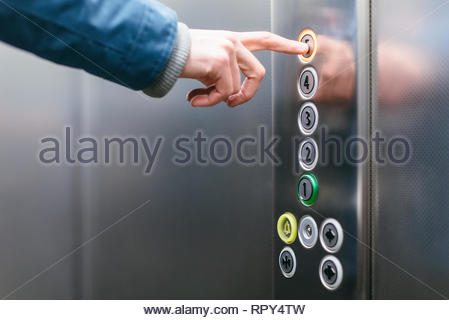 Close up photo of forefinger of adult man pressing the fifth floor button in the elevator/ elevator use, space for copy space, human hand. - Stock Photo