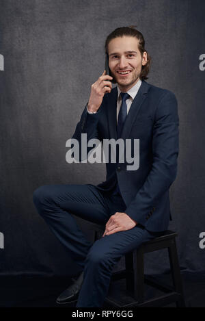 Young businessman in a stylish suit seated on a stool chatting on a mobile phone smiling at the camera with a happy friendly expression against a dark - Stock Photo