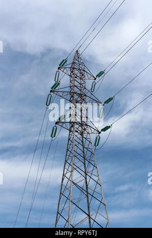 Tall power line utility pole made of metal pipes with multiple electrical wires connected with glass insulators on cloudy blue sky background - Stock Photo