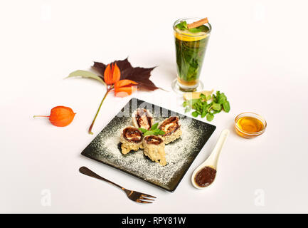 View of fresh oriental dessert on black plate decorated with physalis. Sweet sushi roll cooking prepared for client in oil with chocolate sauce and ic - Stock Photo