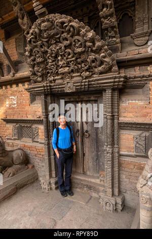 Nepal, Kathmandu, city centre,  Jyatha Marg, Chhusya Bahal, tourist standing below ancient carved torana above temple doorway - Stock Photo