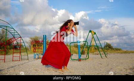 Beautiful girl taking picture on the sea beach in red dress - Stock Photo