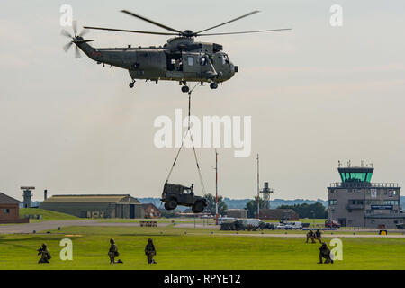 Royal Navy Westland Sea King HC4 helicopter lifting a Land Rover during the Commando Assault demonstration at RNAS Yeovilton, UK Air Day on 26/7/14. - Stock Photo