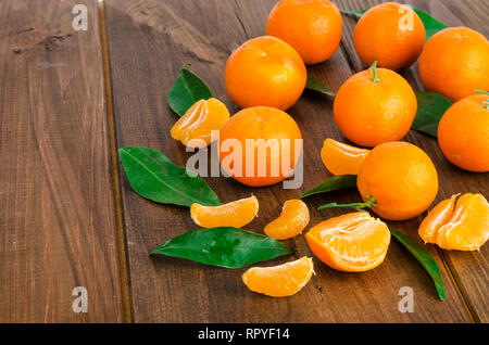 Bunch of fresh tangerines or mandarins and leaves on wooden table. Studio Photo - Stock Photo