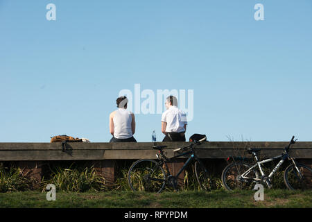 Hampstead Heath, London, UK. 23rd February, 2019. The Met Office is predicting temperatures in the UK could break records this weekend, with high pressure from Europe bringing dry and sunny weather.   In picture, 2 young men relax in the sun.  © Byron Kirk Credit: Byron Kirk/Alamy Live News - Stock Photo