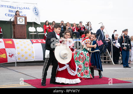 'Abrazo children,' two from the United States and two from Mexico, perform the ceremonial hug of friendship between the two countries as part of the annual Washington's Birthday celebration in Laredo, Texas, and Nuevo Laredo, Tamaulipas, Mexico. The ceremony is held on the international bridge between the two cities. - Stock Photo