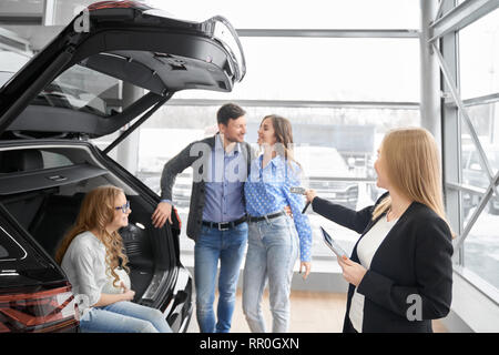 Manager of car dealership working with clients, holding folder and giving car keys to buyers of vehicle. Couple standing, posing, daughter sitting in car trunk, smiling. - Stock Photo