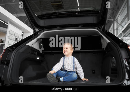 Handsome, cute little boy sitting in luggage space of big, new black automobile. Pretty child posing, looking away and smiling. Happy kid observing vehicle in car trunk. - Stock Photo
