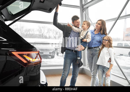 Happy family observing new, expensive black car in modern showroom. Father holding kid on hand, opening car trunk, parents standing with children, smiling, looking at car. - Stock Photo