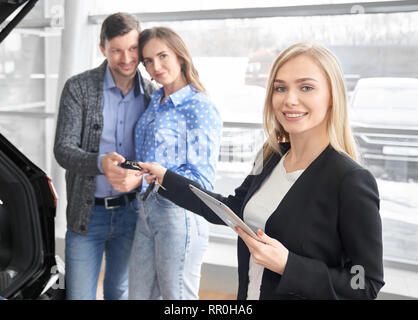 Car dealer giving keys to buyers of automobile, holding folder. Happy pretty couple standing behind, taking keys, smiling. Beautiful blonde woman looking at camera and posing. - Stock Photo
