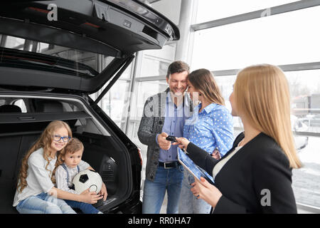 Car dealer of dealership showrrom working with clients, holding folder and giving car keys to buyers of vehicle. Couple standing, posing, daughter and son sitting in car trunk, hugging, smiling. - Stock Photo