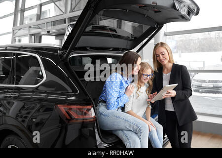 Mother and daughter sitting in car trunk, communicating with manager of dealer showroom. Car dealer working with clients, showing information on gadjet. Women smiling, posing. - Stock Photo