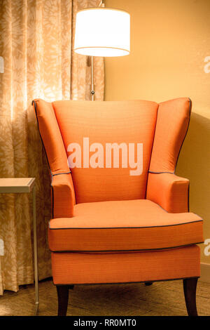 Orange upholstered armchair and light in comfortable interior setting - Stock Photo