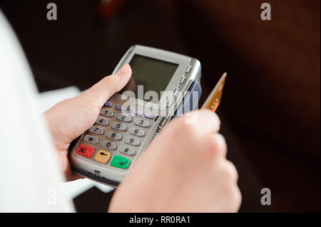 Hand swiping debit card on pos terminal - Stock Photo