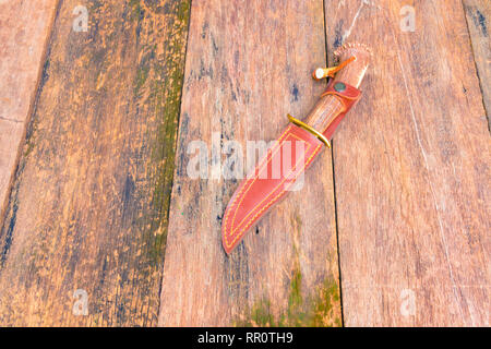 Knife for hiking in sheath brown leather on wooden vintage background with copy space add text - Stock Photo