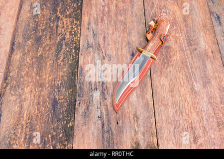 Knife for hiking on sheath brown leather with wooden vintage background with copy space add text - Stock Photo