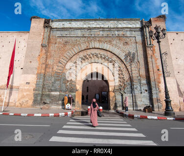 Arab woman crossing a pedestrian path in front of City gate Bab Agnaou . Entrance to the old city - the medina of Marrakech, Morocco - Stock Photo