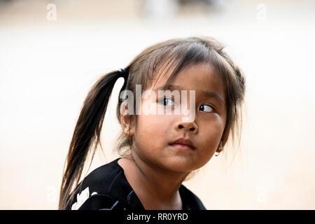 Beautiful spontaneous portrait of a Laotian young girl in Luang Prabang. - Stock Photo