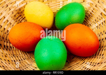 Five colorful easter eggs in a straw basket isolated - Stock Photo