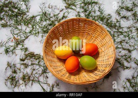 Five colorful easter eggs in a straw basket on top of snow and grass isolated egg hunt - Stock Photo