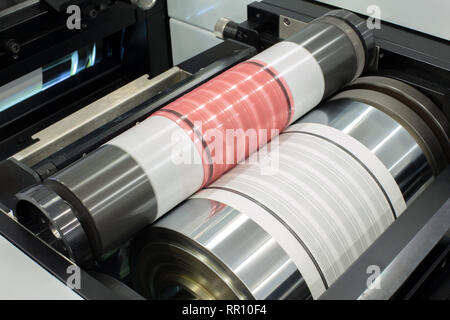Flexography printing process on in-line press machine. Photopolymer plate stuck on printing cylinder, substrate is sandwiched between the plate and th - Stock Photo