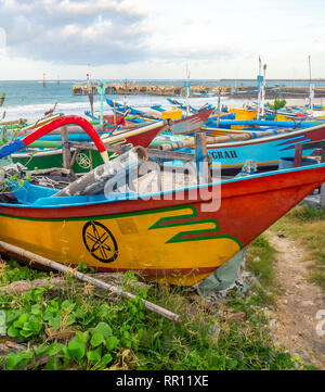 Jukung traditional wooden canoes used for fishing on the  at Jimbaran Bay Bali Indonesia. - Stock Photo