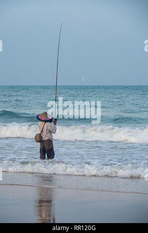 Lone fisherman wearing a conical hat fishing with a rod off the beach at Jimbaran Bay Bali Indonesia. - Stock Photo