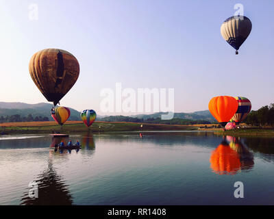 Colorful hot air balloons flying over river - Stock Photo