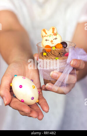 Woman's hands holding transparent plastic cup with chocolate mousse in one hand and decorated Easter egg in the other - Stock Photo