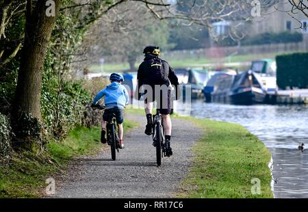 A man and a boy cycle on the path by the Peak Forest Canal near Furness Vale - Stock Photo