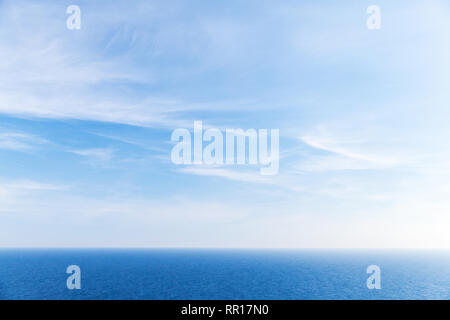 Blue sky background, white clouds over still ocean - Stock Photo