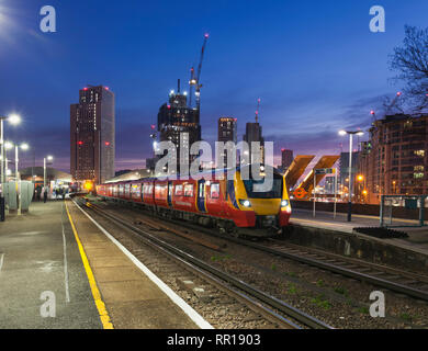 A South Western railway class 707 calling at  Vauxhall, London at dusk with the London skyline behind - Stock Photo