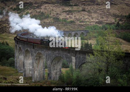The traditional Jacobite steam train on the high Glenfinnan railway viaduct in a landscape in the west Highlands of Scotland, UK. - Stock Photo