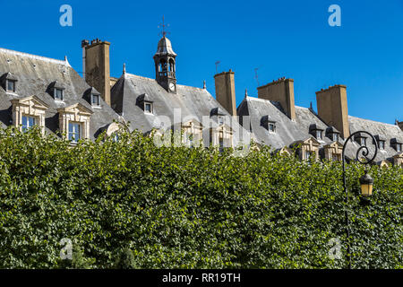 The grey slate roofs attic rooms and chimneys of buildings surrounding the Place des Vosges in the fashionable  Le Marais district of Paris , France - Stock Photo