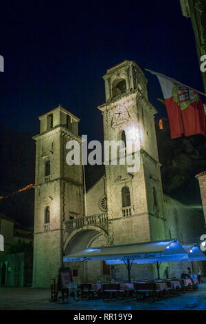 St Tryphon's Cathedral (Katedrala Sv Tripuna) in the eponymous square (Trg Sv Tripuna) and the city fortifications illuminated above: Kotor, Montenegr - Stock Photo