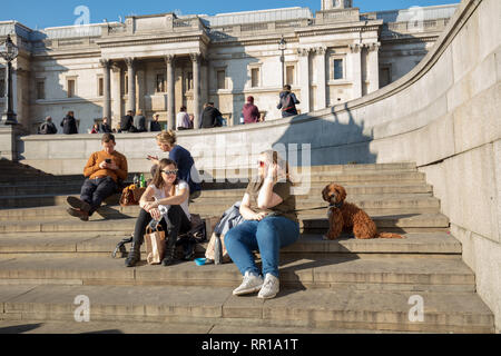 People, family and friends, enjoying a fun day, walking, sitting and relaxing on Trafalgar Square of London, UK, on a warm spring like day in February - Stock Photo