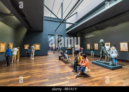 People viewing  impressionist and post-Impressionist masterpieces on the 5th floor of  Musée d'Orsay , a converted railway station in Paris ,France - Stock Photo