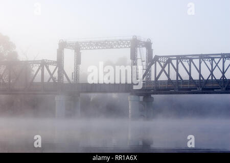 Old lift-span bridge over the Murray River, down stream from Mildura, photographed on a foggy winters morning, built in 1928. - Stock Photo