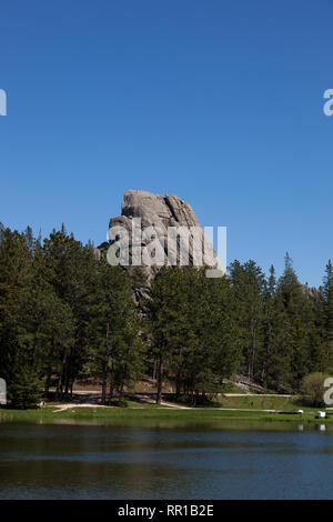 The unique rock formation of Little Devils Tower rising above the tree line and Sylvan Lake in Custer State Park, South Dakota. - Stock Photo