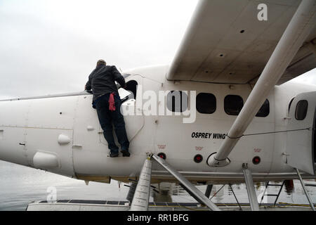 A float plane pilot servicing his plane on a dock at a lake near the town of Stanley Mission, in northern Saskatchewan, Canada. - Stock Photo