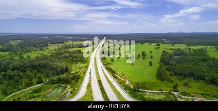 Aerial panorama of highway passing through countryside on bright sunny day. Collombatti, New South Wales, Australia - Stock Photo