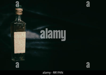 Single poison bottle against a black and blue background with dark green toning. Horizontal aspect. - Stock Photo