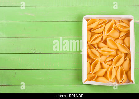 Raw pasta shells on a green wooden background with copy space for your text. Top view - Stock Photo