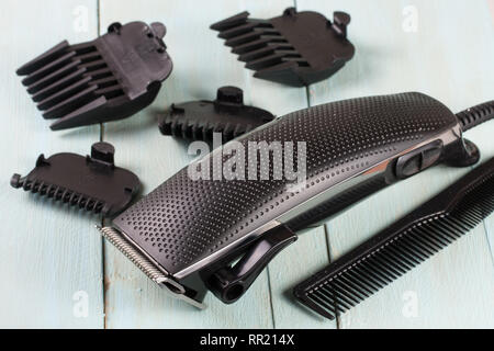 hair trimmer with comb on the wooden background - Stock Photo