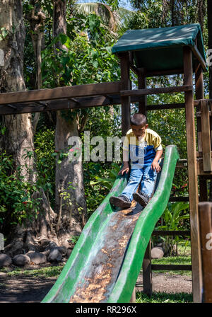 young latin boy playing on slide in Guatemalan playground - Stock Photo