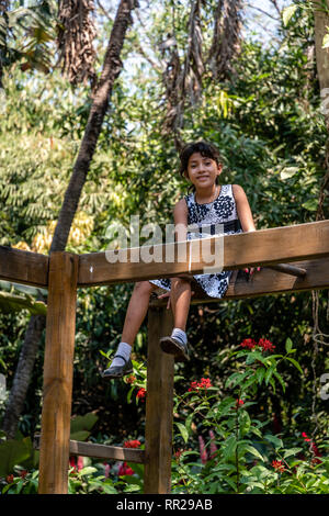 young latin girl sitting on monkey bars in Guatemalan playground - Stock Photo