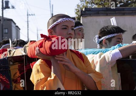 Tokyo, Japan. 24th Feb, 2019. Participants dressed in women's kimonos and wearing makeup, run from house to house to chase away evil spirits during the Ikazuchi no Daihannya festival. Festival volunteers carry 6 containers from the Shinzoin Temple around the neighborhood to chase away evil spirits.The origins of this annual event are disputed, but the legend tells the priest of Shinzoin Temple visited house to house to prevent the spread of cholera during the late Edo era. Another legend of a man who lived in the neighborhood dressed in women's kimono to scare away the bad spirits for h - Stock Photo