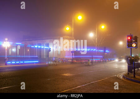Southport, Merseyside. 24th February, 2019. UK Weather. Hazy, foggy, misty start to the day with light drizzle as early morning city centre traffic lights up the damp pavements. Ambulance blue lights from passing emergency vehicle leave reflections on the road surface. Credit: MWI/AlamyLiveNews. - Stock Photo