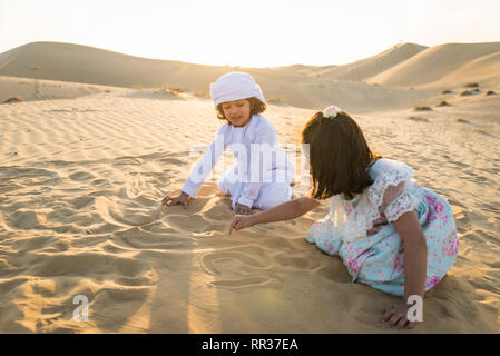Arabian family with kids having fun in the desert - Parents and children celebrating holiday in the Dubai desrt - Stock Photo